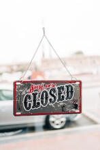 Rectangular Shaped Signboard With Sorry And Closed Titles Hanging On Transparent Wall In City