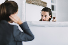 Young Female In Formal Outfit Looking At Mirror And Adjusting Hair While Preparing For Workday In Morning
