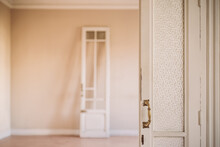 Old Fashioned White Wooden Opened Door With Ornamental Handles In Retro Style In Empty Apartment