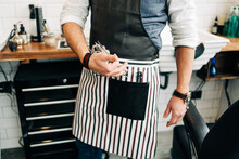 Crop Unrecognizable Male Barber With Scissors And Comb In Striped Apron In Hairdressing Salon