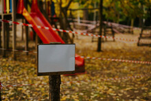 Empty Sign With Blank Space Located Near Playground Fenced With Red And White Attention Tape During Coronavirus Epidemic