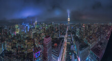 From Above Aerial Cityscape Of New York City With Glowing Towers And Illuminated Streets Under Cloudy Night Sky