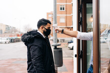 Crop Anonymous Male Hairdresser In Sterile Mask Measuring Temperature Of Colleague With Infrared Thermometer At Door Of Barbershop
