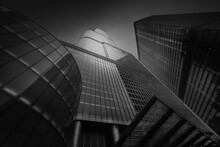 From Below Exterior Of Modern High Rise Buildings With Glass Mirrored Walls Under Dark Blue Sky On Street Of Chicago In USA, Black And White Picture