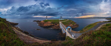 Scenic View Of Small Island With Lighthouse Called Faro De Cabo Mayor Connected With Coastline By Bridge Under Dramatic Cloudy Sky At Sunset Time In Santander In Spain