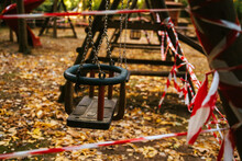 Empty Wooden Swing On Playground Fenced With Red And White Attention Tape During Coronavirus Pandemic