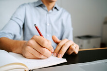 Unrecognizable Crop Male Entrepreneur Sitting At Table And Writing In Notebook While Planning Business Project