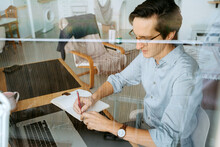 Male Entrepreneur Sitting At Table And Writing In Notebook While Planning Business Project