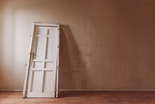 White Wooden Door With Shabby Surface Placed In Old Empty Room At Daytime