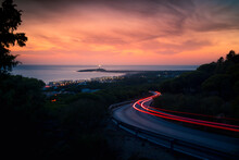 Spectacular Scenery Of Winding Road With Light Trails And Coastal City Near Sea Under Sunset Sky In Cadiz