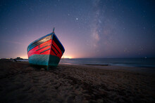 Low Angle Of Wooden Boat Moored On Sandy Shore Near Sea On Background Of Night Starry Sky In Long Exposure In Cadiz