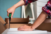 Crop Faceless Female Sitting On Floor And Screwing Screws In Wooden Board While Assembling New Furniture At Home
