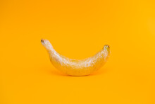 Delicious Ripe Banana Covered With Transparent Plastic Wrap Representing Industrial Agriculture Concept On Bright Yellow Background