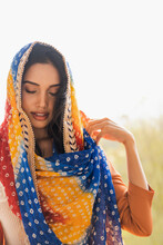 Young Ethnic Indian Female In Traditional Colorful Headscarf With Eyes Closed While Standing Against Blurred Tropical Yard
