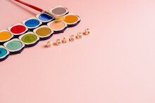 Composition With Paintbrush Placed Near Colorful Palette Of Watercolor Paints With Small Cubes Forming Word Colours On Pink Background