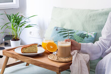Unrecognizable Crop Female Sitting On Bed With Cup Of Coffee And Tray Served With Sponge Cake And Glass Of Juice While Having Breakfast At Home