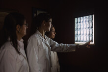 A Group Of Female Doctors Are Looking A X-ray In A Dark Room With The Light Off And One Is Pointing It
