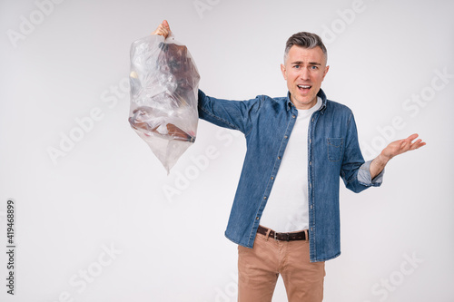 Disappointed mature man holding a bag full of plastic bottles for recycling isolated over white background