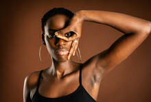 African American Woman Looking At Camera And Gesturing Mask Near Eye Against Brown Background