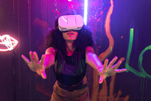 Shocked Female Wearing VR Goggles Touching Air While Experiencing Cyberspace In Studio With Neon Illumination