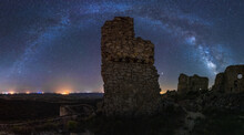 From Below Picturesque Landscape Of Ancient Ruined Castle On Meadow Under Milky Way On Starry Sky At Night
