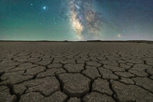 Drought Cracked Lifeless Ground Arid Terrain With Starry Sky At Night
