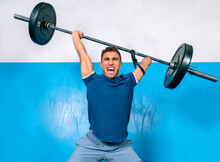Powerful Male Athlete Without Hand Screaming While Lifting Heavy Weight During Functional Training Near Sports Equipment In Gymnasium