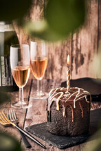 Delicious Chocolate Cake With Burning Candle Served On Slate Board On Table With Glasses Of Champagne In Cafe