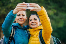 Delighted Female Hikers Taking Selfie On Smartphone While Standing In Nature During Trekking