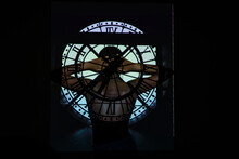 Back View Of Unrecognizable Black Female With Hands Behind Head Standing Under Shade Of Clock In Dark Room