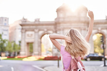 Back View Female Teenager With Hands Raised Standing In Sunshine During Trip In Madrid