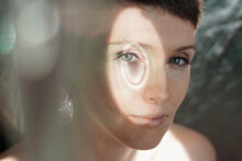 Through Glass Of Peaceful Adult Lady With Short Hair Looking At Camera On Sunny Day