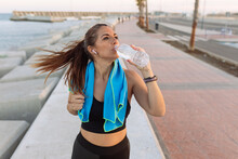 Young Fit Female Jogger With Towel On Neck Drinking Water From Bottle While Having Break After Running On Urban Waterfront