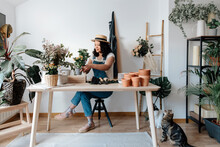 Young Female Horticulturist In Straw Hat Creating Bouquet On Table With Assorted Tools At Home
