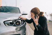 Upset Young Female Driver In Casual Outfit Having Phone Conversation On Road And Inspecting Damages On Modern Car After Crash
