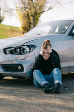 Full Length Of Sad Young Female Driver In Casual Clothes Sitting On Road Near Expensive Damaged Car And Crying After Accident