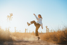 Side View Of Active Young Lady In Trendy Outfit Dancing In Dry Fiends Against Cloudless Blue Sky In Countryside