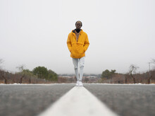 Ground Level Full Body Of African American Male With Hands In Pockets Standing On Asphalt Roadway Among Leafless Trees And Snow