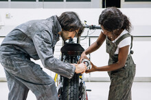 Side View Of Diverse Technicians In Workwear Repairing Muffler Of Custom Motorbike While Working Together In Bright Workshop