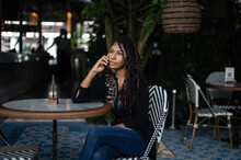 Young Attractive Afro Latina Woman Speaking On A Smartphone In A Restaurant