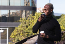 Smiling Young Black Male In Casual Clothes Sending Voice Message On Smartphone While Standing On Terrace Of Modern Building With Cup Of Takeaway Coffee In Sunlight