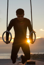 Determined Young Asian Male Athlete Doing Exercise On Gymnastic Rings During Outdoor Workout Against Cloudy Sundown Sky