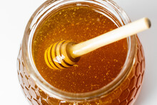 From Above Closeup Of Dipper Stirring Fresh Aromatic Golden Honey In Glass Jar