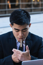 Confident Asian Male Entrepreneur In Formal Clothes Lighting Up Cigar In City Street