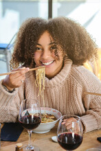 Happy Young Ethnic Female With Curly Hair Enjoying Delicious Asian Ramen While Having Dinner In Restaurant