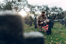 Full Body Sorrowful Soldier In Camouflage Outfit Kneeling Down In Front Of Grave In Military Cemetery On Early Autumn Day