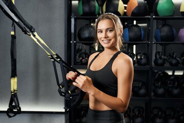 Fototapeta na wymiar Smiling young woman doing exercise with trx system.