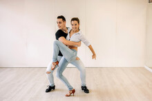 Content Skilled Couple Performing Ballroom Dance During Lesson In Bright Spacious Hall And Looking Away