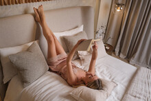 From Above Happy Female In Sleepwear Lying On Bed And Enjoying Interesting Book In Evening At Weekend