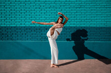 Full Body Athletic Barefoot Woman In White Loose Pants And Top Raising Leg In Sunlight Against Green Brick Wall